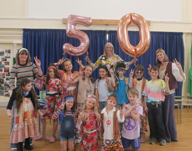 Staff and pupils in fancy dress at Grange CE Primary School, with headteacher Phillipa Summers holding the balloons