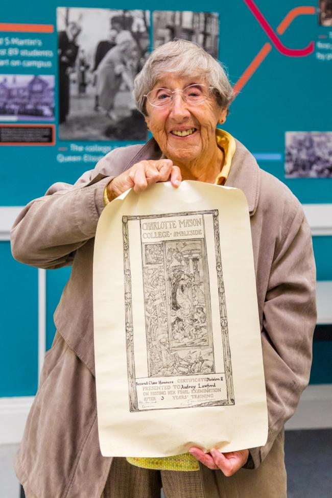 Retired teacher Audrey Wright holding her Charlotte Mason College graduation certificate at the University of Cumbria's Ambleside campus