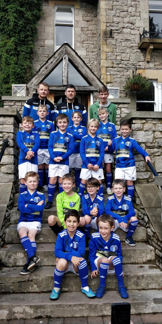 Wattsfield Youth U9s on the steps of new kit sponsors Romneys