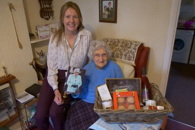 CCHA's Pamela Armstrong presents 100-year-old Noreen Thwaites with a birthday hamper and flowers