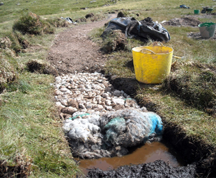 BUILDING PATHS: The fleeces of the Herdwick sheep  are rolled up and placed in the trench before the aggregates
