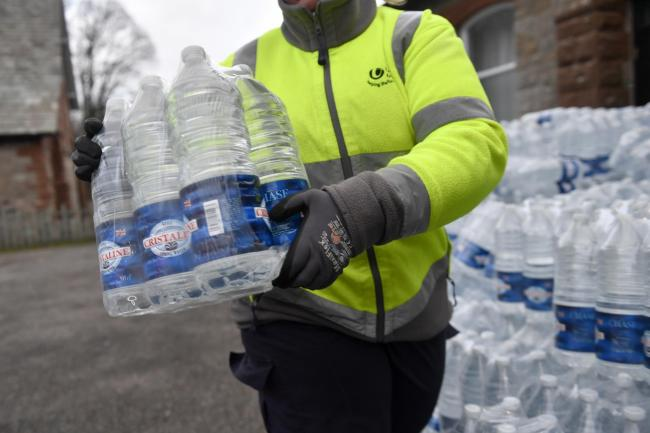 United Utilities staff handout bottles of water to residents of Pooley Bridge. Storm Ciara caused damage to a main water supply pipe in the County: 10 February 2020.STUART WALKER.