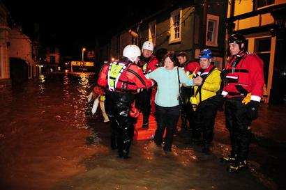 A woman is helped from an inflatable boat after being rescued in Cockermouth