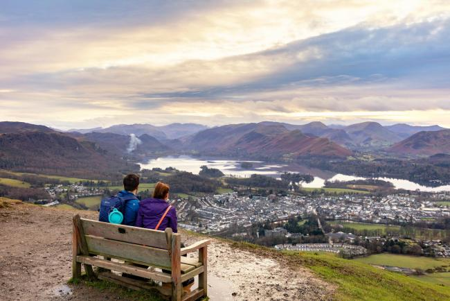 Tourists enjoying a view across Keswick and Derwentwater