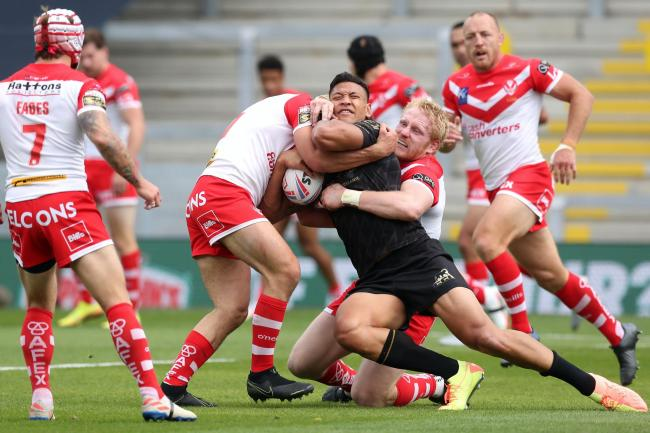 Israel Folau, centre, is tackled by St Helens' James Bentley, centre left, and James Graham