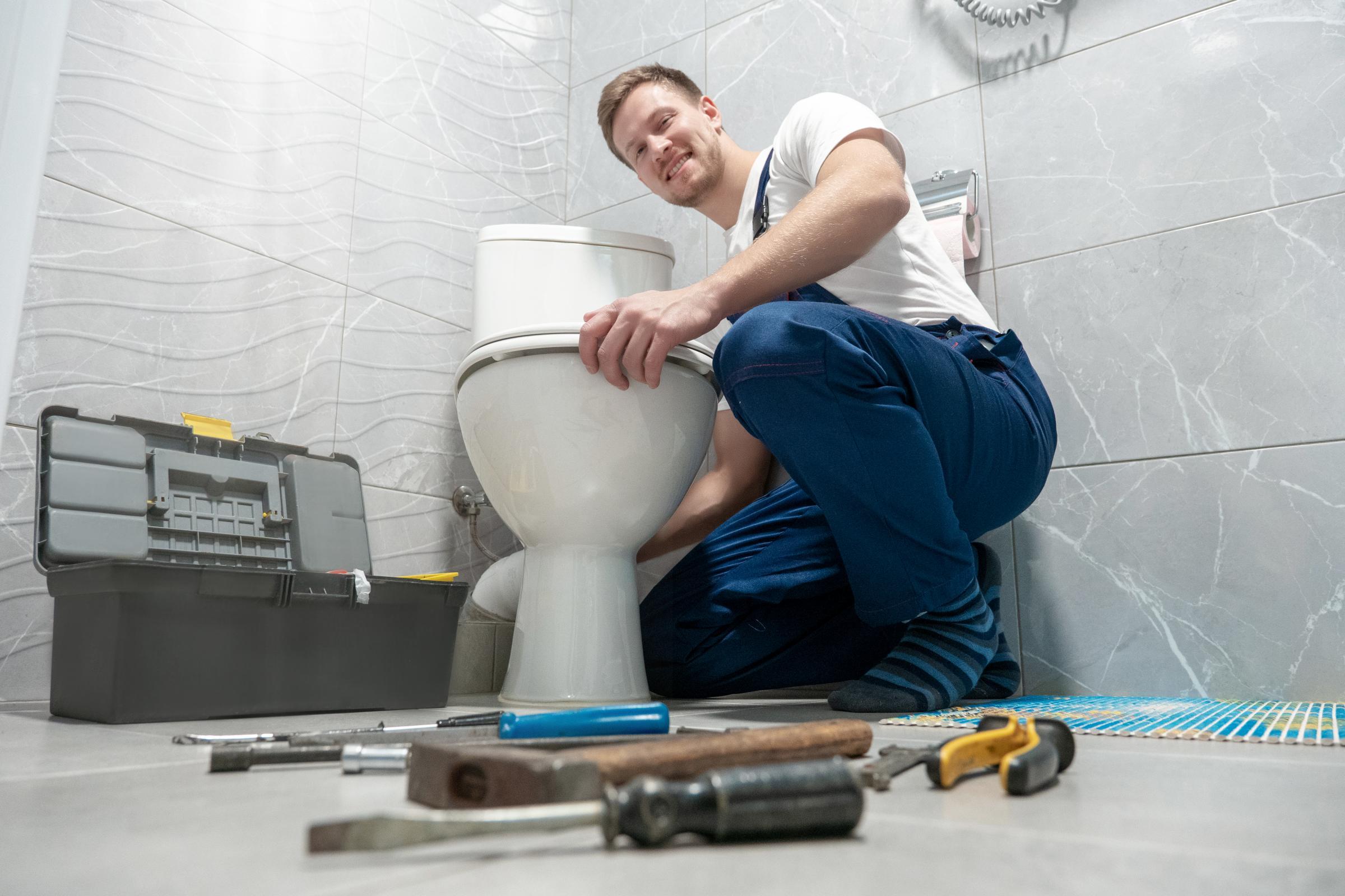smiling man plumber in uniform repairing toilet bowl using instrument kit looks happy professional repair service..