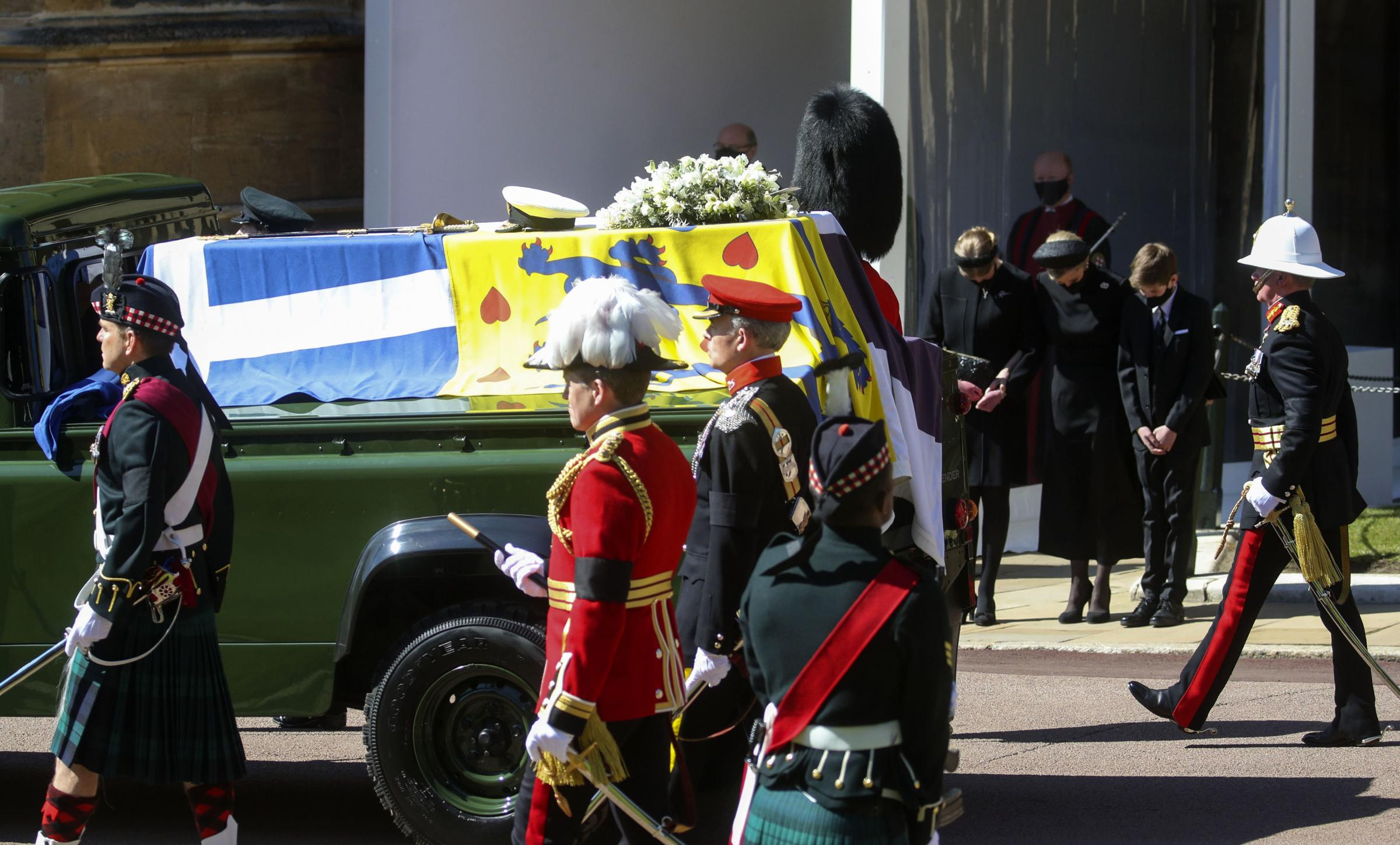 The Duke of Edinburghs coffin, covered with his Personal Standard, is carried on the purpose built Land Rover Defender drives past (left to right) Lady Louise Windsor, the Countess of Wessex and James, Viscount Severn with heads bowed, at the Galilee