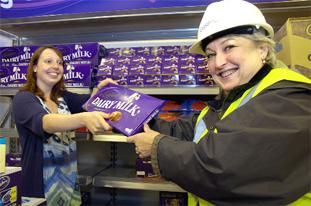 TAKING SHAPE: Anna Murphy, assistant manager of the new Cadbury store presents centre manager Mandy Dixon with a bar of chocolate.