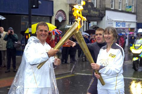 John Roelich takes the Olympic flame from Cate Davies in Kendal Town Centre.