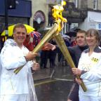 The Westmorland Gazette: John Roelich takes the Olympic flame from Cate Davies in Kendal Town Centre.