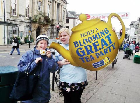 Elaine Bamford of Marie Curie (right) enjoying a brew in Kendal with a shopper