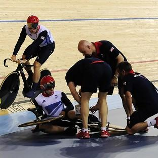Sir Chris Hoy (left) rides past Philip Hindes following his fall