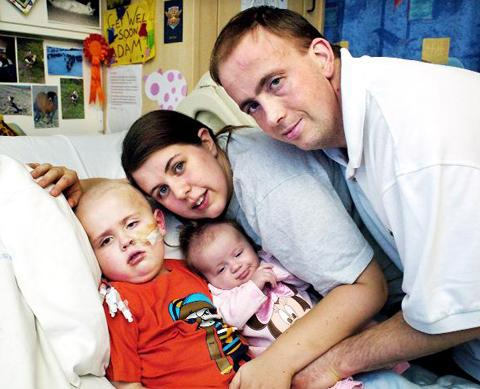 Adam with his mum, dad and little sister Olivia in hospital in Manchester