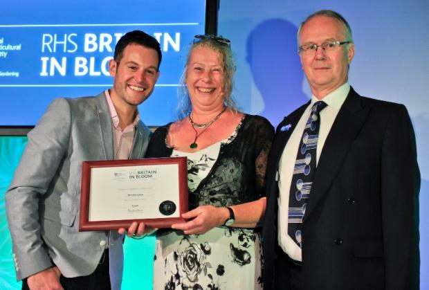 Matt Baker, left, presents a silver award to Lisa Greasley and Adrian Faulkner, representing Windermere and Bowness