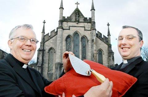 Father Hugh Pollock and Father Andrew Dawson with the trowel used to lay the foundation stone at Holy Trinity