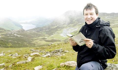 Stuart Maconie peruses his Wainwright guide in the Lakeland Fells