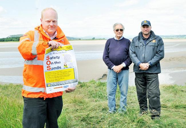 Mike Davis, training officer for Bay Search and Rescue, Queen's Guide Cedric Robinson and Nigel Capstick, station officer for Arnside Coastguard, with a copy of The Westmorland Gazette Safety on the Sands poster