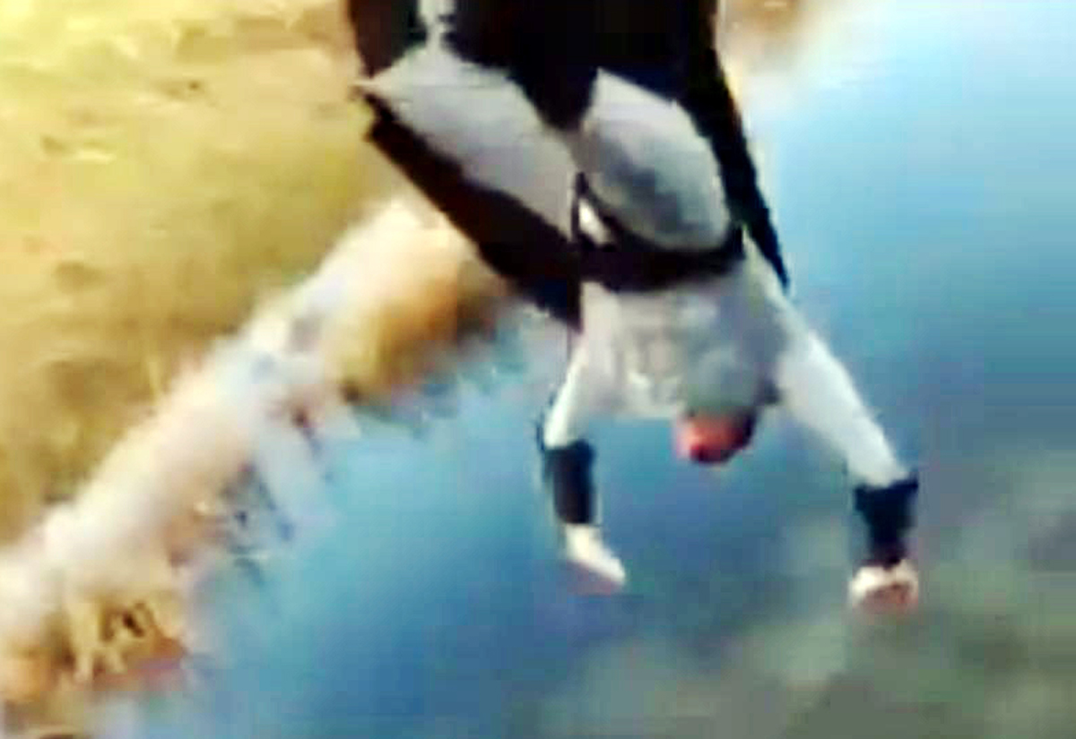 A teenager dressed as Batman dives into water in the Lyth Valley