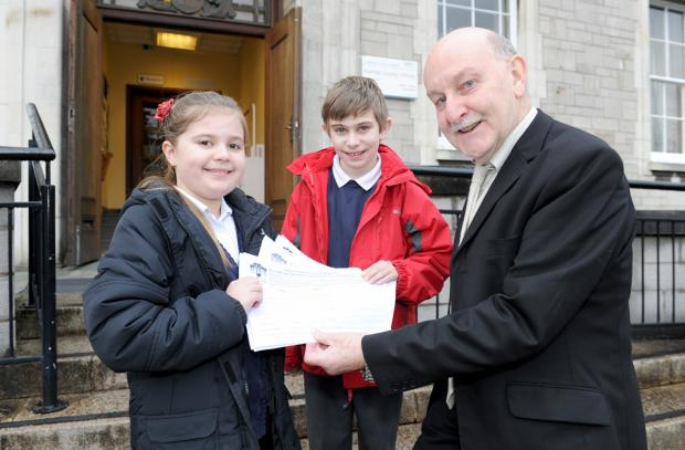 Connor Davis and Darcey Looker hand over the petition to Cumbria County Councillor Geoff Cook, chairman of South Lakes Local Committee