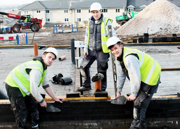 The Westmorland Gazette: Russ Carradus, centre, laying bricks with his nephew Peter Carradus, left, and Benjamin Porter, at the Cragg Close development in Sandylands, Kendal