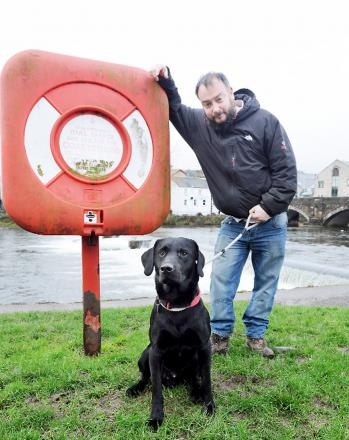 John Walker beside an empty life buoy container with his Labrador Reggae who he rescued from the raging River Kent when the animal got into difficulties at Goosehome