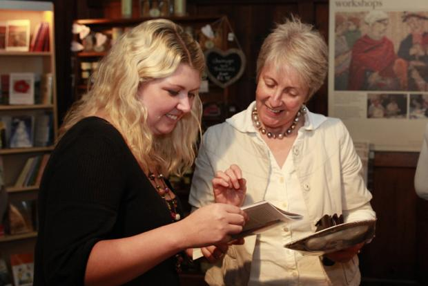 Quaker Tapestry staff member Lisa Moore provides information for visitor Carole Butcher
