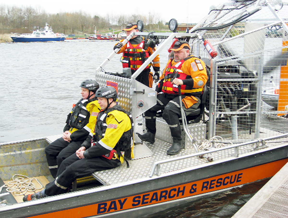 Members of the Bay Search and Rescue team demonstrate the newly created flat-bottomed boat created from a US air boat