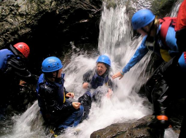 Young people enjoying ghyll scrambling with the Brathay Trust