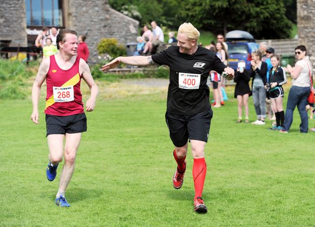 A relieved Iwan Thomas holds out a hand for Boff Whalley of Chumbawamba