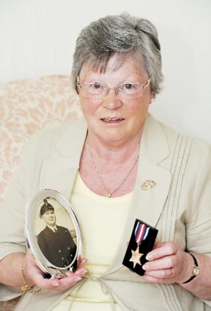 Daughter Margaret with the medal and a picture of her father