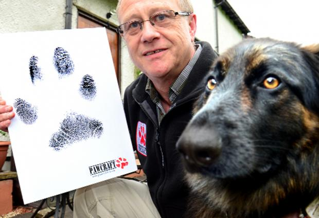 Mark Knowles with his pet Oushba – and an enlarged print of her paw print