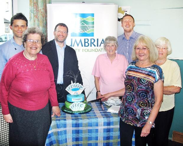 A cake is cut to celebrate the success of Cumbria's Winter Warmth fund