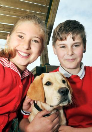 Charlotte Thompson, aged 10, and Liam Noble, 11, with guide dog puppy Magic.