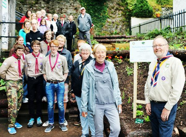 Judy Pickthall (centre), a former Ulverston Mayor and chair of Ulverston in Bloom is seen with Xenolith Explorer Scout Unit leader Bryan Caine (right) and some of the volunteers and wellwishers at the opening of the community garden