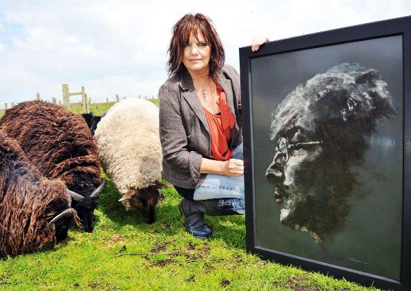 Artist Jill Harrison with her woollen picture of John Lennon – and some sheep