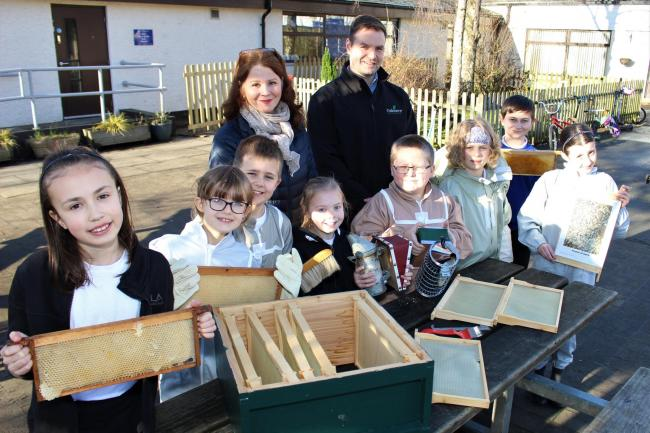 The Bee Team at Heron Hill School prepare their equipment for tending the hives under the watchful eye of Chair of Governors Jacqui Cottam and Matt Hind from Oakmere Homes which is helping to buy a 'bee hut' for the school.  The Bee Team are: (from le