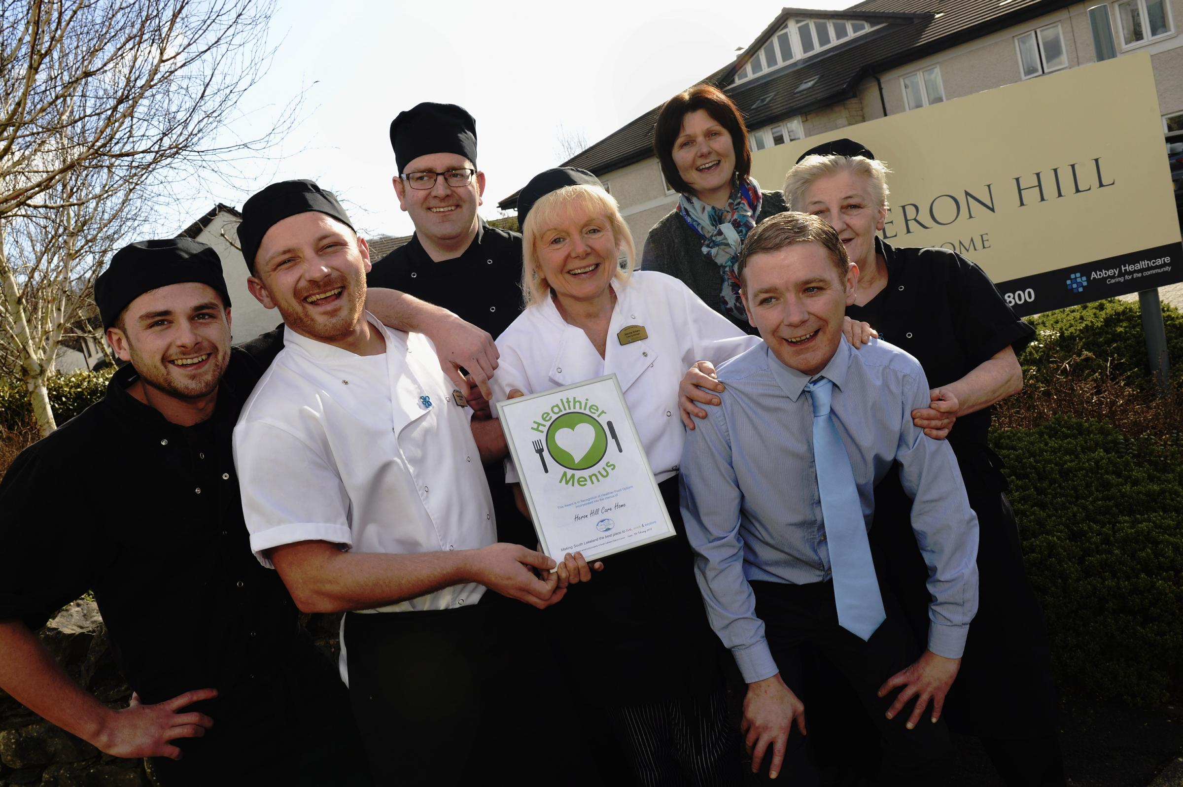 All smiles from kitchen staff members of Heron Hill care home in Kendal who are pictured with manager Adrian Wheawall (front), after receiving a healthy eating award from SLDC's environmental health officer Hilary Fawcett (back right). They are Kurtis