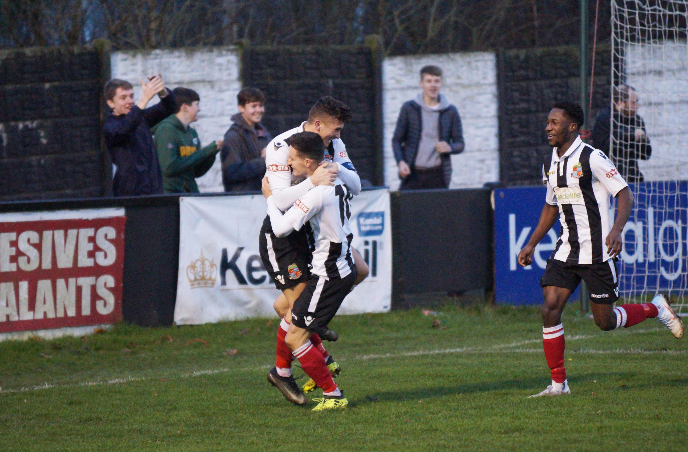 Ben Thomas and Steven Yawson celebrate with Scott Harries after he scored for Kendal