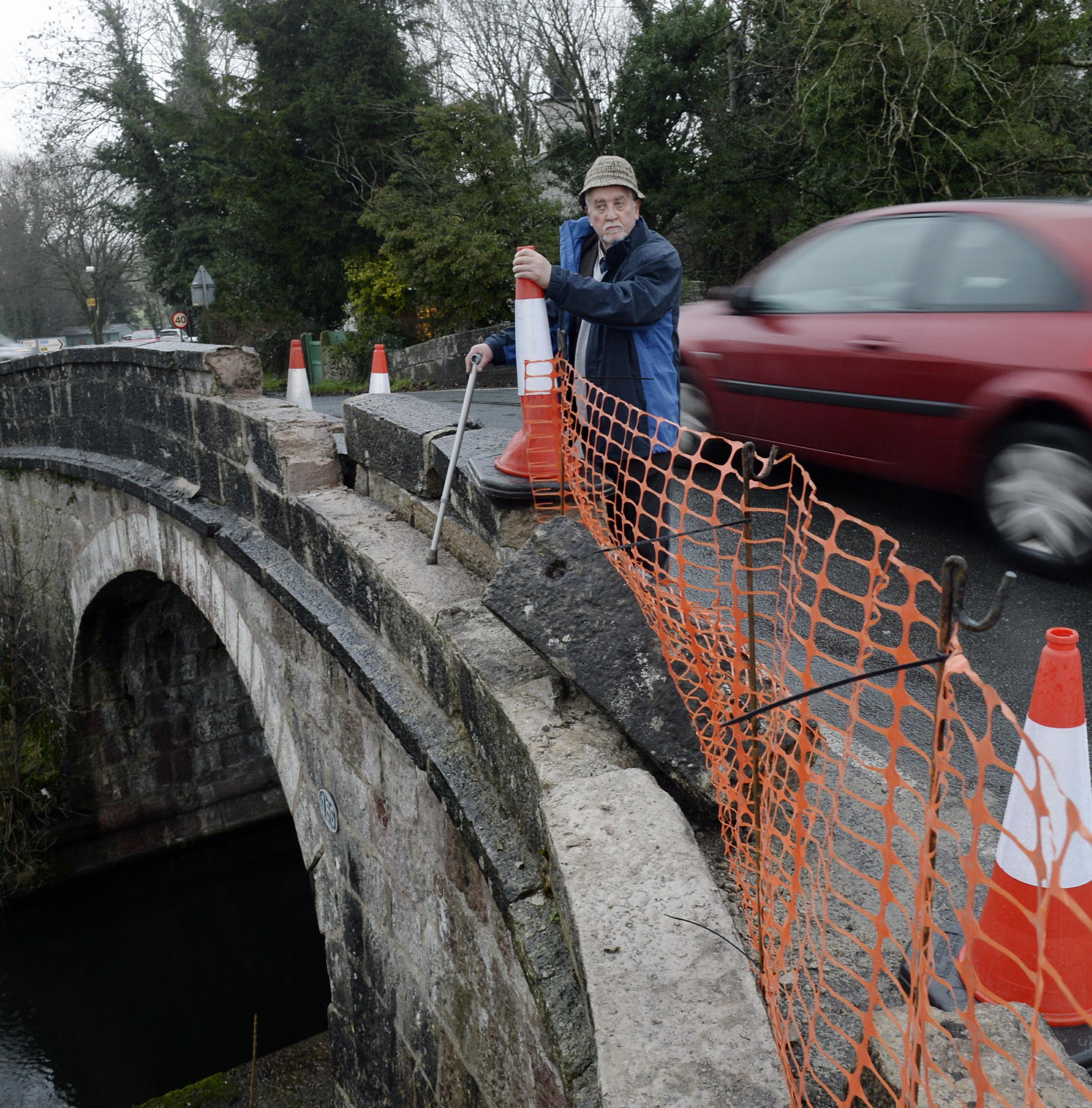 Councillor Roger Bingham looking at damage to the canal bridge at Crooklands near Kendal